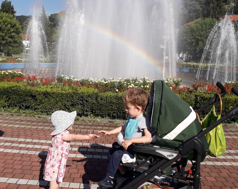 Дети, маленькая девочка и мальчик с фонтаном в красивом медицинском центре Banja Koviljaca здоровья спа стоковое фото rf