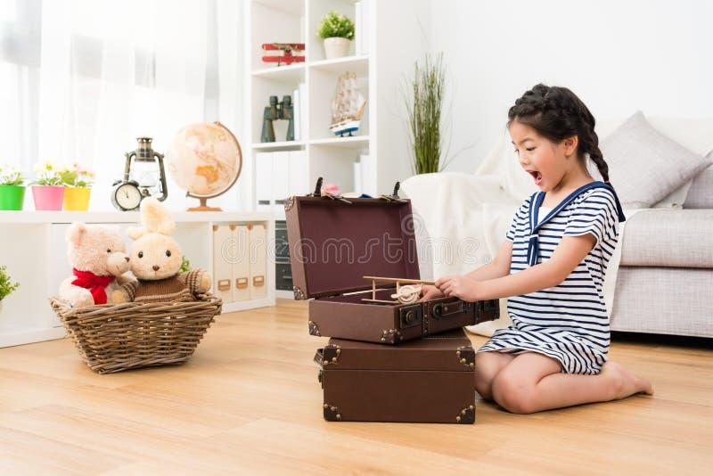 Дети маленькой девочки раскрывая винтажный чемодан стоковые фотографии rf