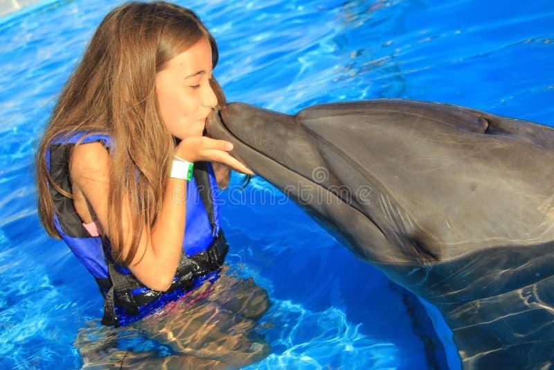 Дети маленькой девочки целуя ребенк стороны шикарного флиппера дельфина усмехаясь счастливого плавают дельфины носа бутылки стоковая фотография rf