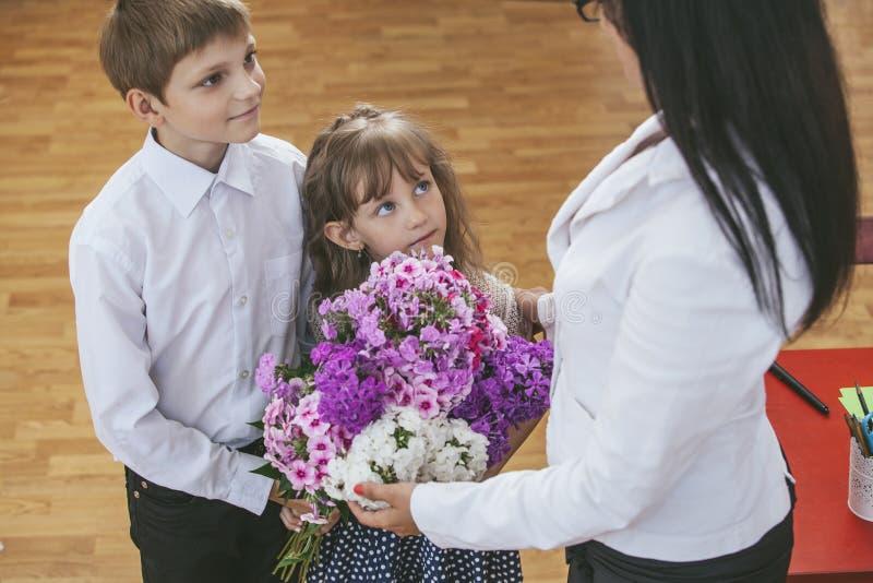 Дети мальчика и девушки дают цветки как школьный учитель стоковая фотография