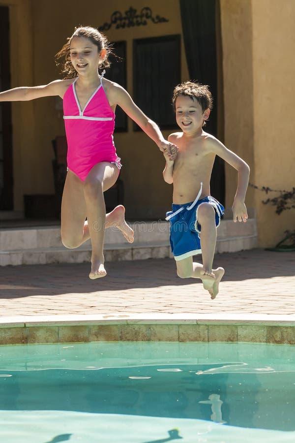 Дети мальчика и девушки скача в бассейн стоковое фото