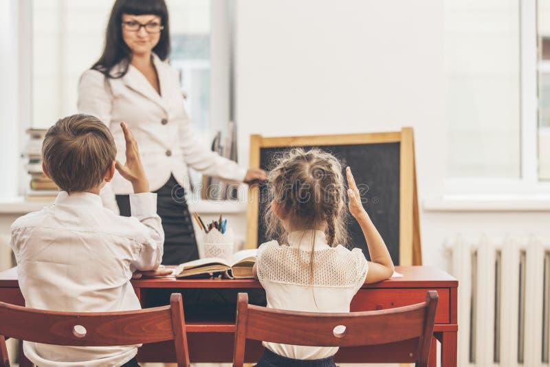 Дети мальчика и девушки с учителем в школе стоковое фото rf