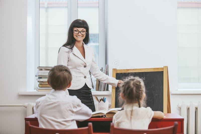 Дети мальчика и девушки с учителем в школе стоковая фотография rf