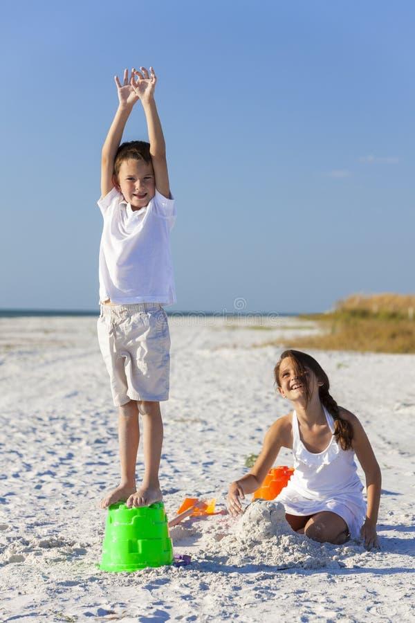 Дети, мальчик, девушка, брат & сестра играя на пляже стоковые изображения rf