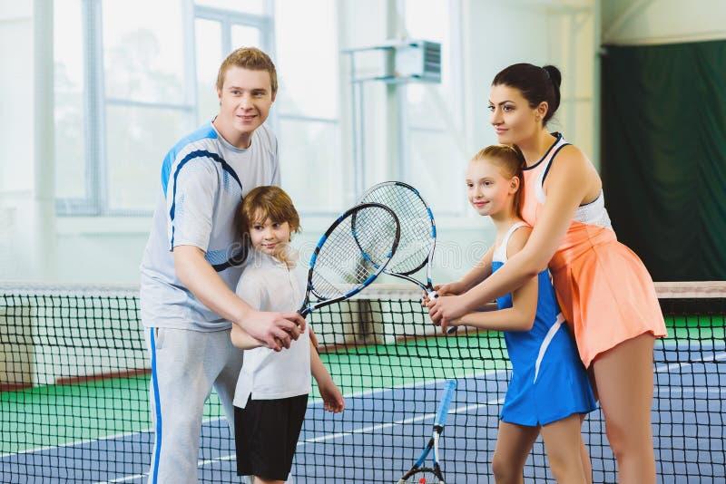 Дети молодой женщины и человека или тренера уча как сыграть теннис на суде крытом стоковая фотография rf