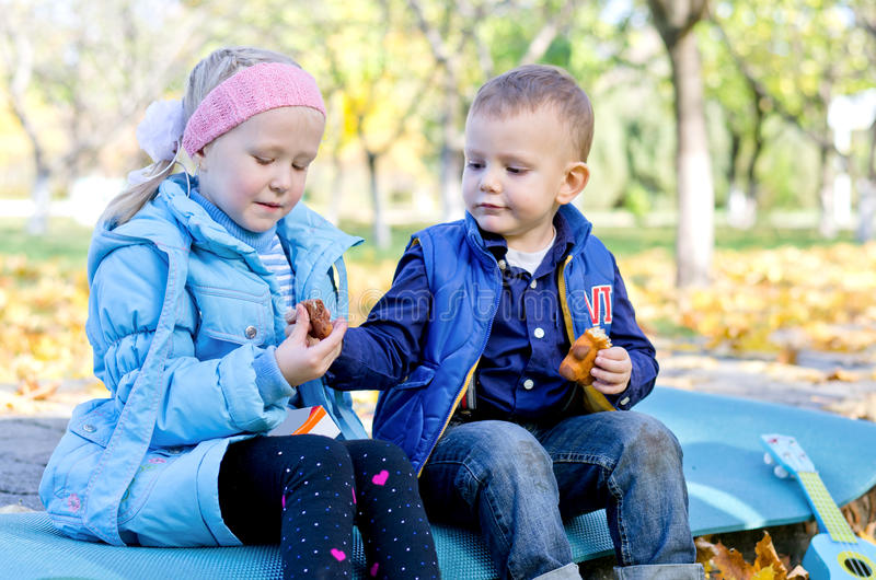 Дети наслаждаясь заедк в парке стоковое фото