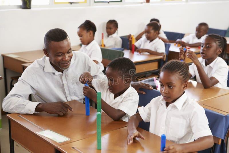 Дети начальной школы порции учителя подсчитывая с блоками стоковое изображение rf