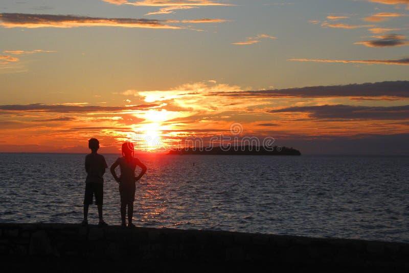 Дети на заходе солнца стоковая фотография rf