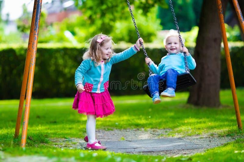 Дети на качании спортивной площадки стоковое изображение rf