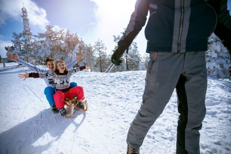 Дети на снеге sledding и наслаждаясь на солнечный зимний день стоковая фотография rf