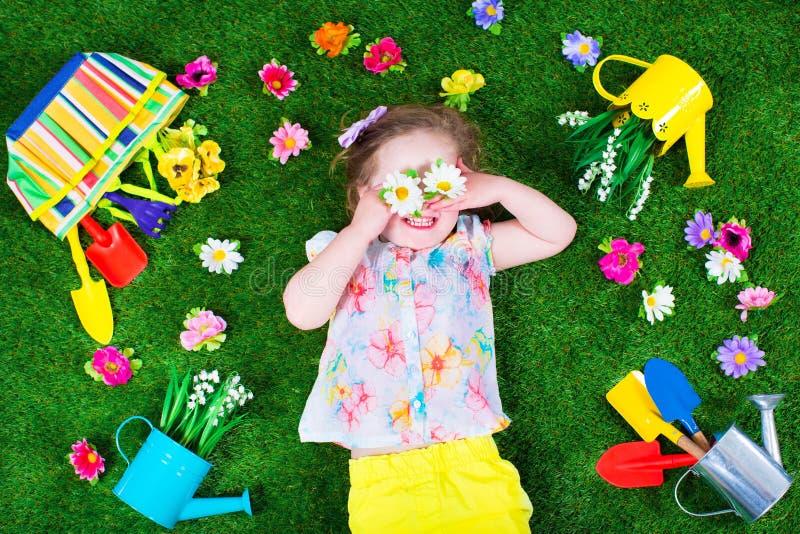 Дети на лужайке с садовыми инструментами стоковое изображение