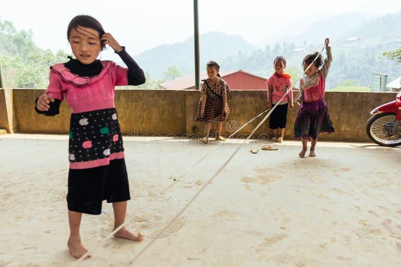 Дети нося розовую веревочку игры футболки скачут на конкретный пол в лете на PA Sa, Вьетнам стоковые изображения