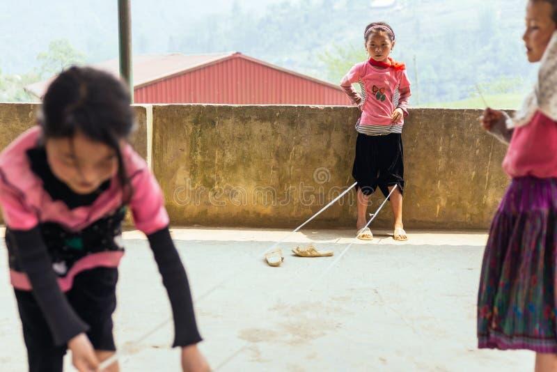 Дети нося розовую веревочку игры футболки скачут на конкретный пол в лете на PA Sa, Вьетнам стоковые фотографии rf