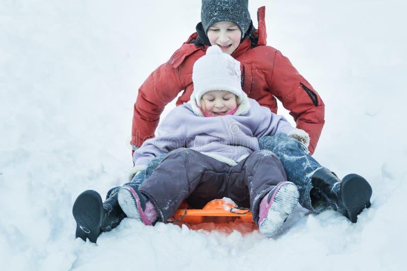 Дети нося теплую одежду имея потеху во время стоковые фото