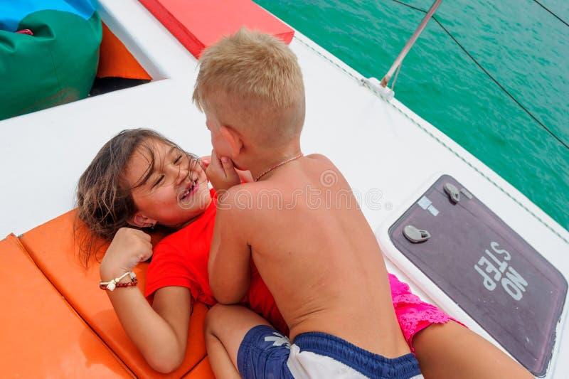 Дети обнимая на шлюпке стоковое фото rf