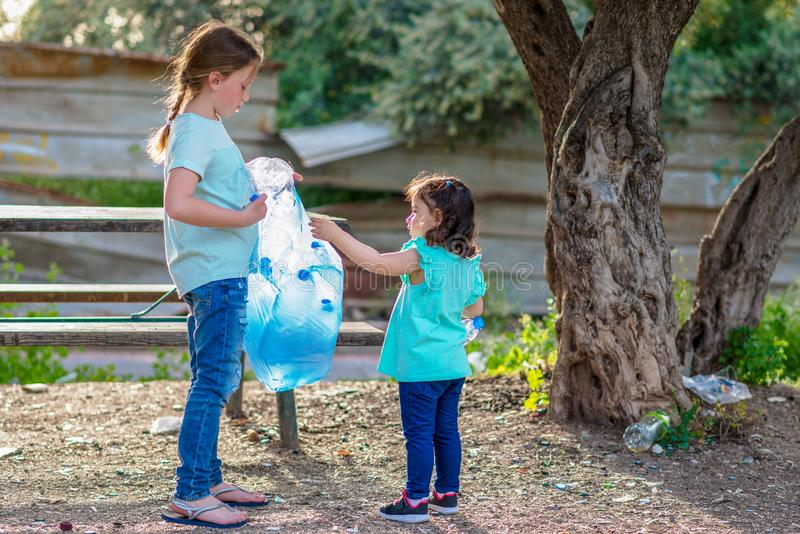 Дети очищая в детях forestVolunteer с сумкой отброса очищая вверх по сору, кладя пластиковую бутылку в повторно использовать сумк стоковые фото