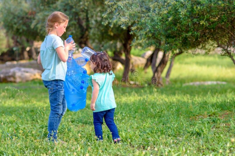 Дети очищая в парке Добровольные дети с сумкой отброса очищая вверх сор, кладя пластиковую бутылку в повторно использовать сумку стоковое изображение