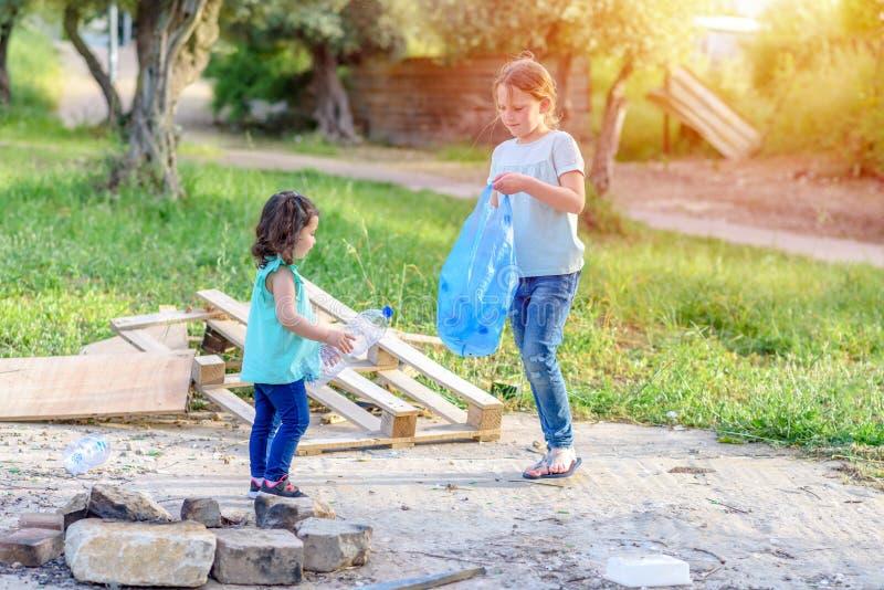 Дети очищая в парке Добровольные дети с сумкой отброса очищая вверх сор, кладя пластиковую бутылку в повторно использовать сумку стоковые изображения