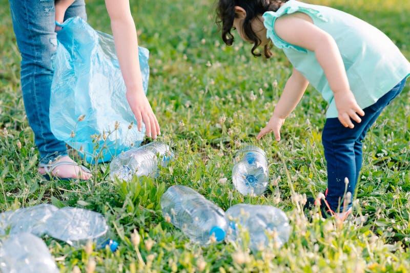 Дети очищая в парке Добровольные дети с сумкой отброса очищая вверх сор, кладя пластиковую бутылку в повторно использовать сумку стоковое фото rf