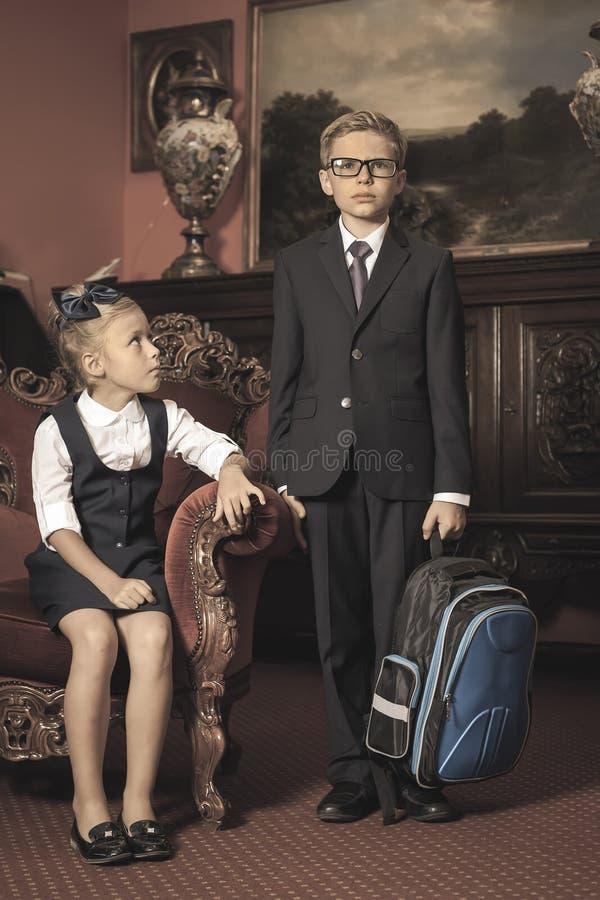 Дети одетые в школьной форме, костюмы школы schoolbag стоковые фото