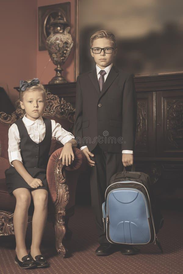 Дети одетые в школьной форме, костюмы школы schoolbag стоковое фото