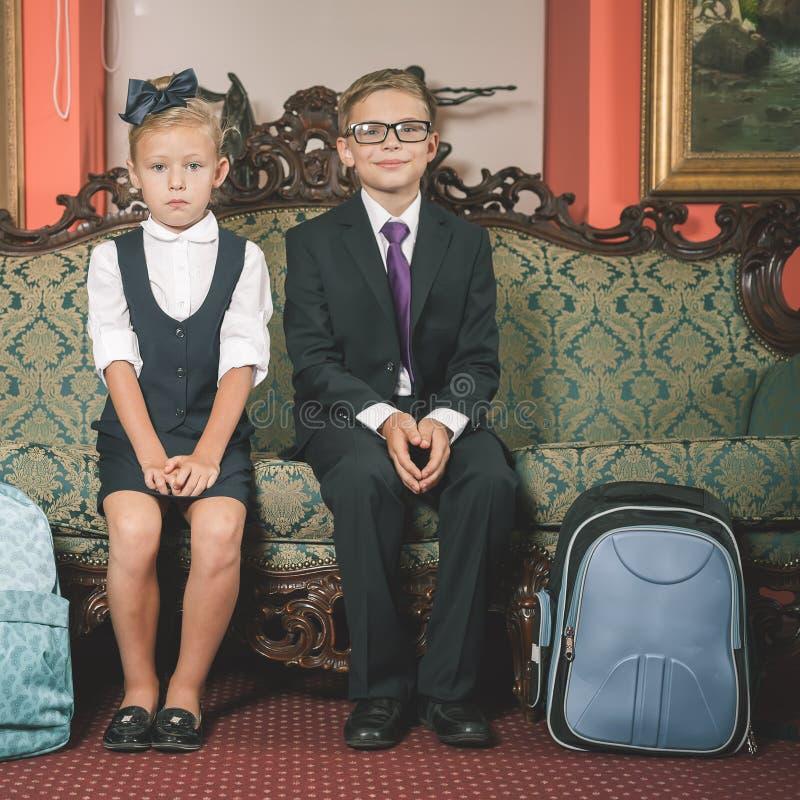 Дети одетые в школьной форме, костюмы школы schoolbag стоковая фотография