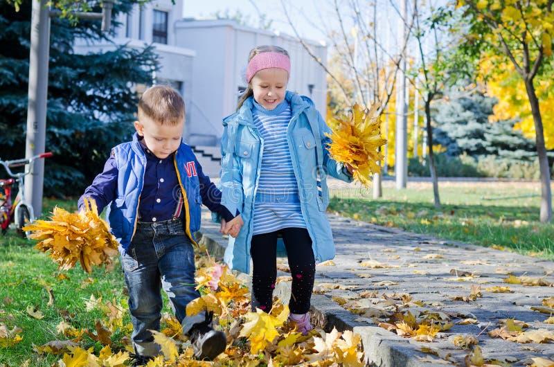 Дети пиная листья осени стоковая фотография
