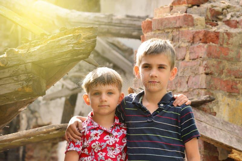 Дети плохих и neschatnye на руинах, который сгорели дома Братья пострадали стихийное бедствие стоковые фотографии rf