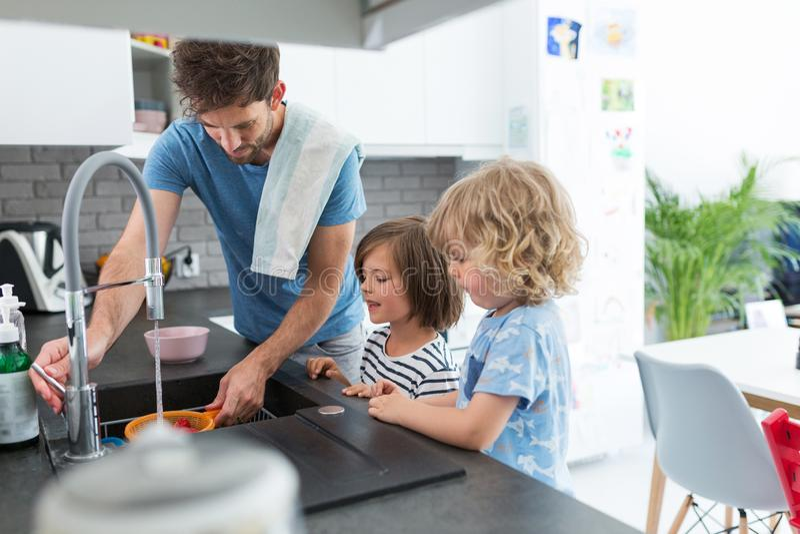Дети помогая отцу в кухне стоковые фотографии rf