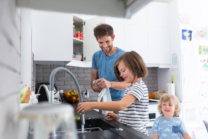 Дети помогая отцу в кухне стоковые изображения rf