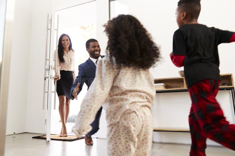 Дети приветствуя и обнимая работая родителей по мере того как они возвращают домашнее от работы стоковые фото