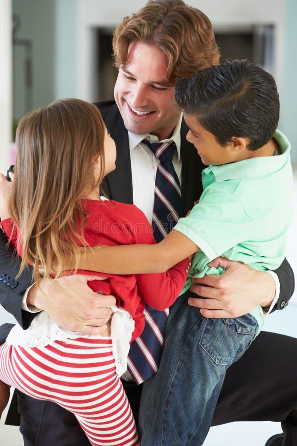 Дети приветствуя отца на возвращении от работы стоковые фото