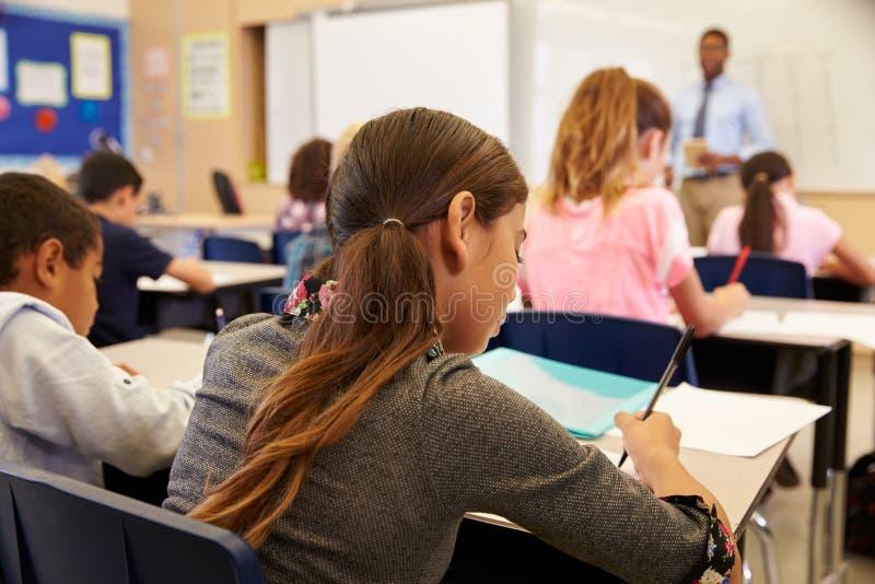 Дети принимая примечания в уроке начальной школы стоковое фото