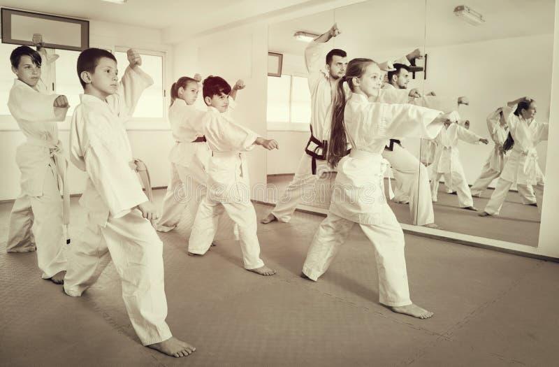 Дети пробуя военные движения в классе карате стоковое изображение