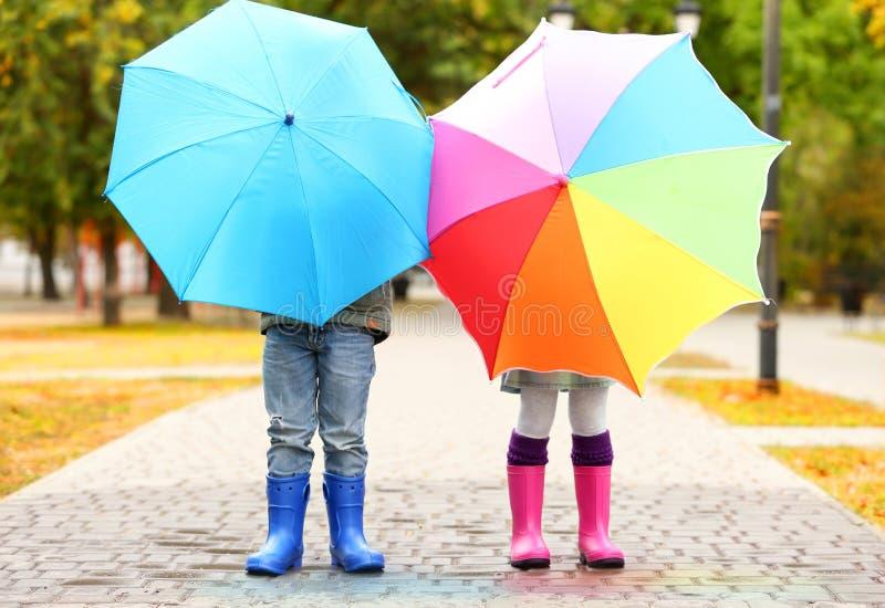 Дети пряча за яркими зонтиками стоковые изображения
