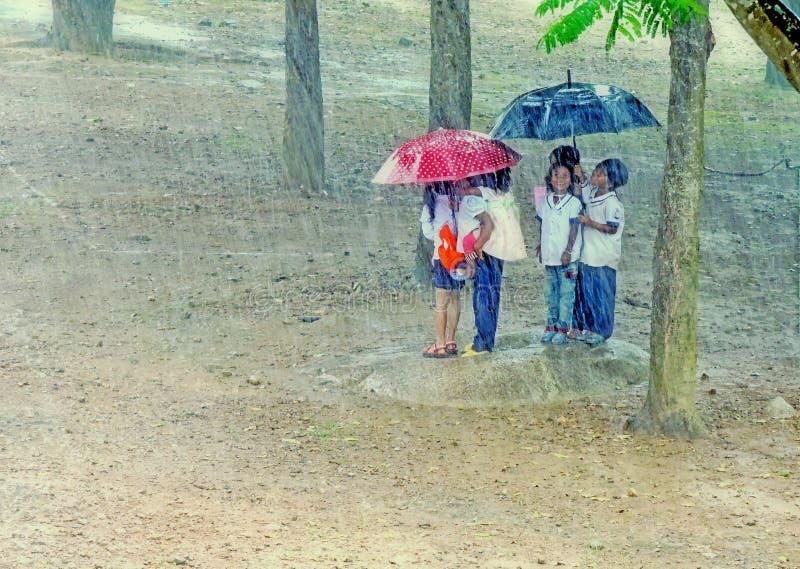 Дети пряча под зонтиком стоковые изображения rf