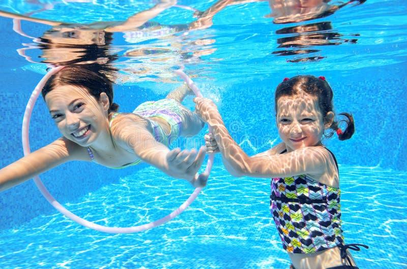 Дети плавают в бассейне подводном, счастливые активные девушки имеют потеху под водой, спорт детей стоковое изображение rf