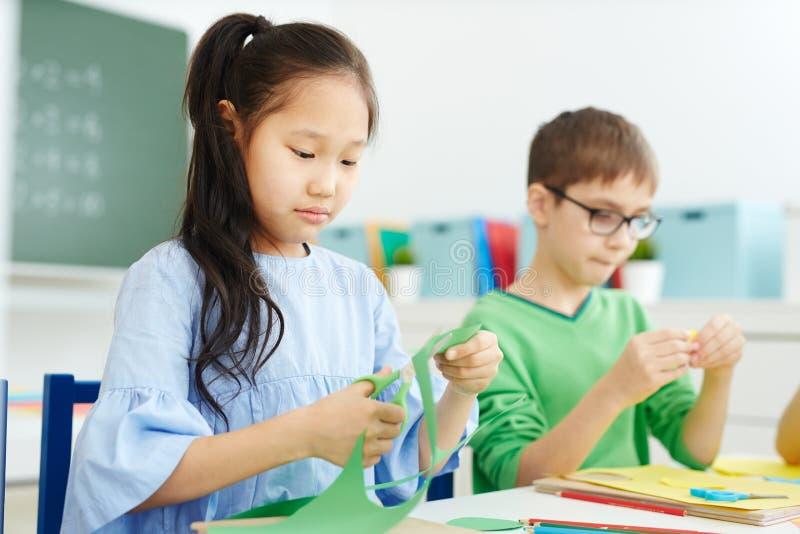 Дети режа бумагу для origami стоковая фотография
