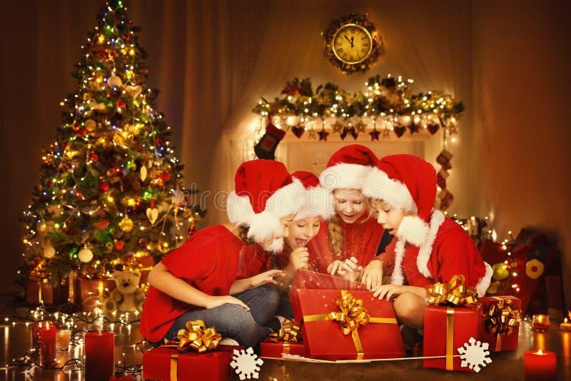 Дети рождества раскрывают присутствующую подарочную коробку, счастливые детей, дерево Xmas стоковая фотография rf