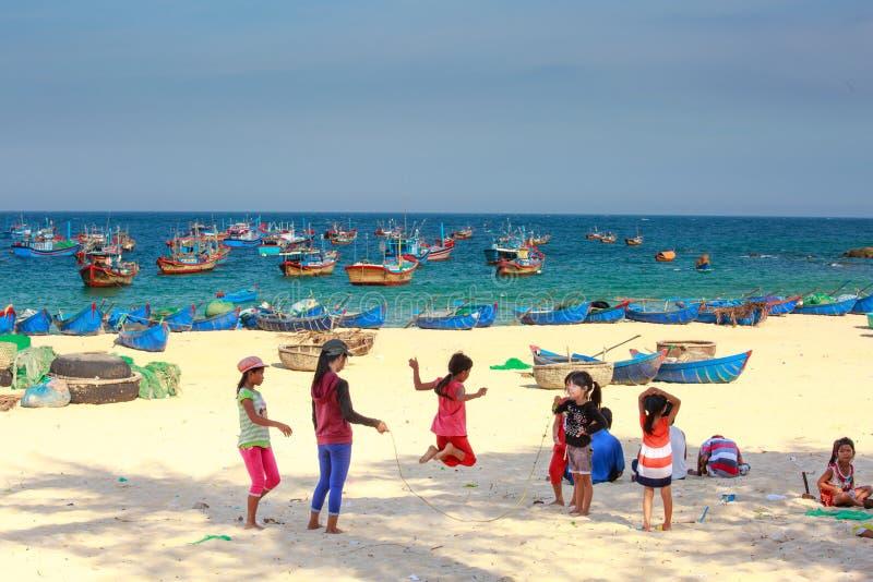 Дети рыбацкого поселка играя веревочку скачки на песочном побережье стоковые изображения rf
