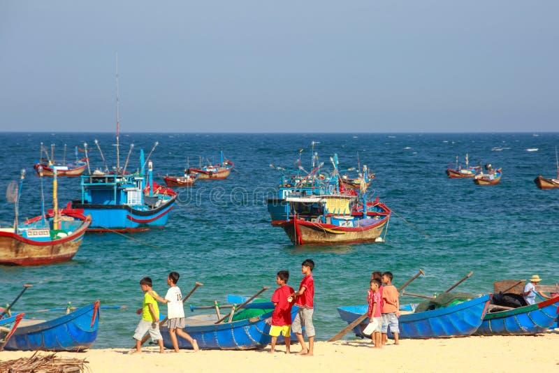 Дети рыбацкого поселка на пляже стоковое изображение rf