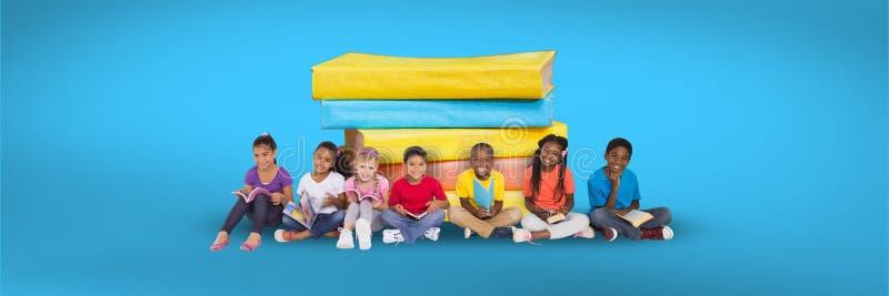 Дети сидя на поле и куче книг с голубой предпосылкой стоковое фото rf