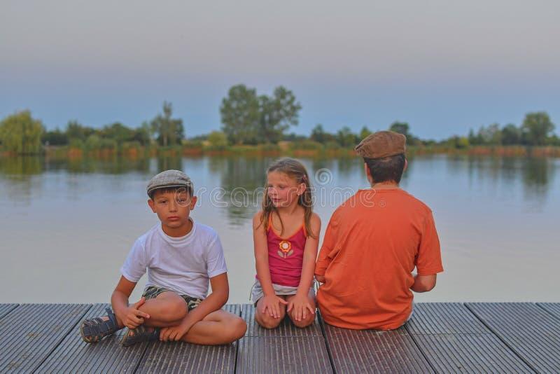 Дети сидя на пристани отпрыски 3 дет различного времени - мальчик подростка, элементарный мальчик времени и усаживание девушки pr стоковое изображение