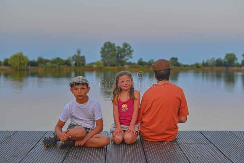 Дети сидя на пристани отпрыски 3 дет различного времени - мальчик подростка, элементарный мальчик времени и усаживание девушки pr стоковое фото