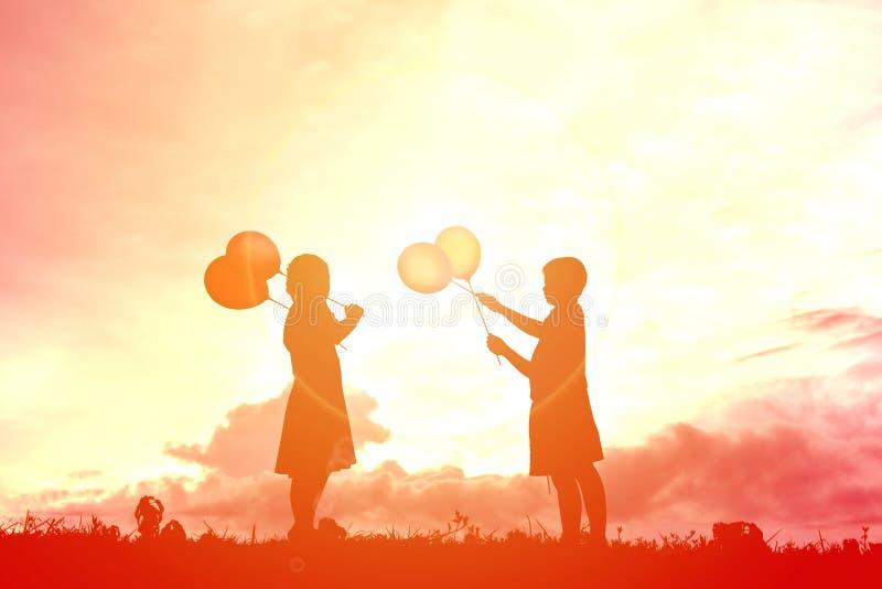 Дети силуэта с воздушным шаром стоковое изображение rf