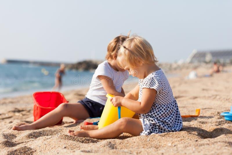 Дети сидя на пляже стоковое фото rf