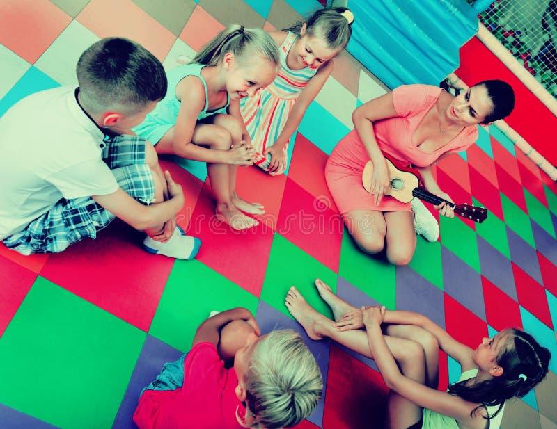 Дети сидя с учителем и слушая к музыке в классе стоковая фотография rf