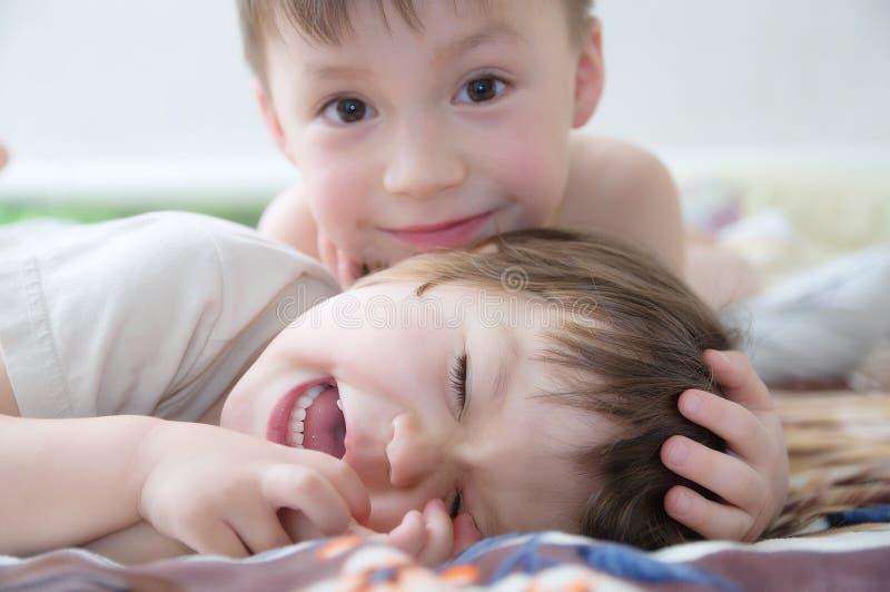 Дети смеясь над, портрет счастливых детей усмехаясь, играя совместно отпрысков, маленькую девочку и мальчика, брата и сестру стоковое фото