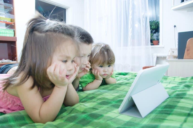 Дети смотря на пусковой площадке лежа на кровати дома Трата времени детей Дети используя таблетку стоковая фотография rf