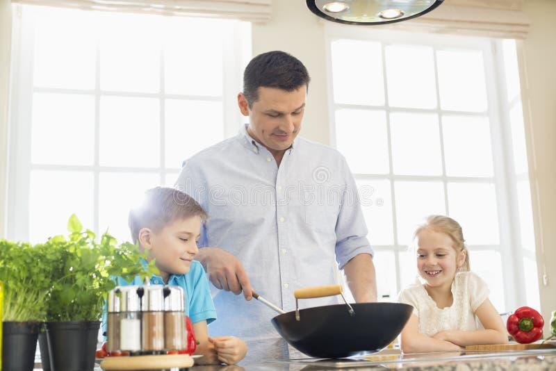Дети смотря отца подготавливая еду в кухне стоковая фотография rf